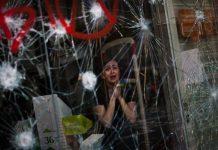 Una mujer observa los destrozos en la huelga general del 29 de marzo de 2012 en Barcelona. / EMILIO MORENATTI (ASSOCIATED PRESS)