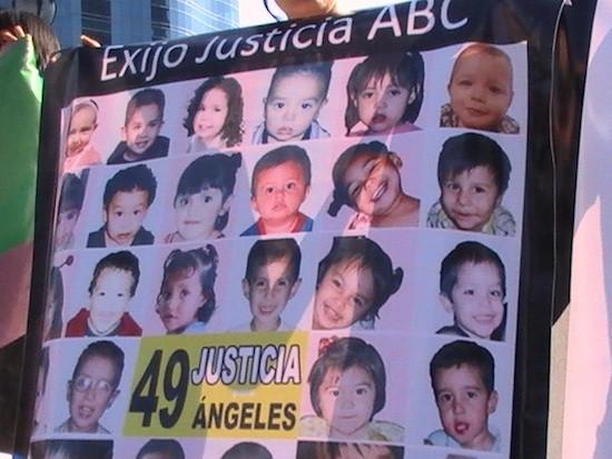 La pancarta muestra los rostros de 49 niños que fallecieron en la guardería ABC.