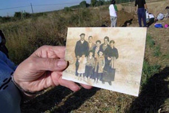 Un familiar muestra la foto de un desaparecido durante una exhumación en Berlangas de Roa, Burgos. © Francisco Etxeberría