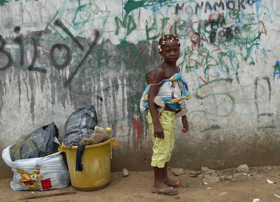 Niña cargando a un bebé en Luanda. Angola dejará de integrar la lista de países menos adelantados en 2015. Crédito: Louise Redvers/IPS.