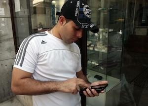 Un joven cubano, luciendo un gorro con inscripciones de Nueva York y una camiseta de la marca Adidas, consulta su teléfono celular en La Habana. Foto: Jorge Luis Baños/IPS