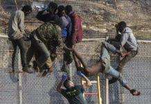 Migrantes y guardia civil en la valla que divide España de Marruecos, en Melilla © AP Photo/Santi Palacios