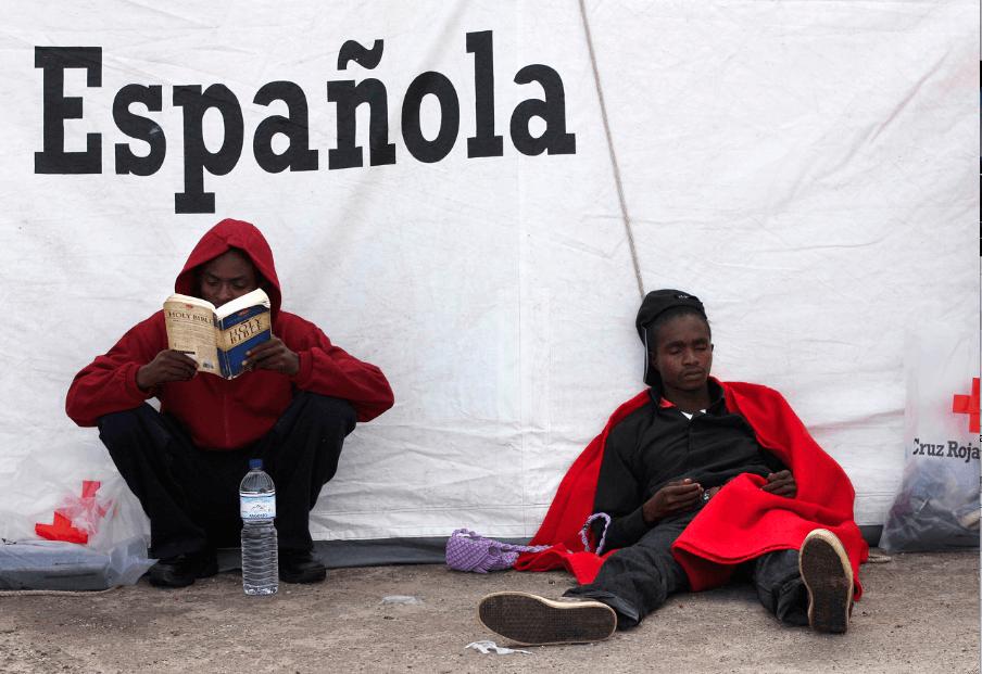 Foto: Andrés Carrasco Ragel. Tarifa (Cádiz). Dos subsaharianos en el puerto de Tarifa tras cruzar el Estrecho en patera. Uno lee la Biblia mientras el otro descansa.