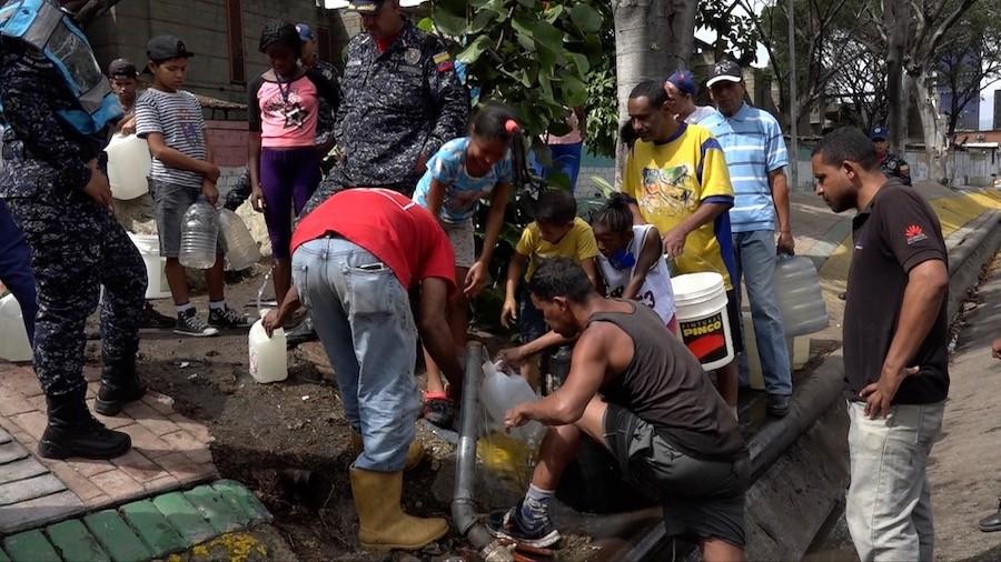 Habitantes del barrio de San Agustín, en el centro de Caracas, recogen agua de una tubería que pasa junto a la principal autopista de la capital de Venezuela, para después acarrearla a sus hogares por las empinadas escaleras que les conducen a ellas desde la avenida. La ausencia de electricidad por entre cuatro y ocho días, agravó las penurias crónicas con el recurso de amplios sectores de la población. Crédito: Humberto Márquez/IPS