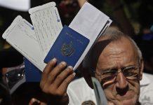 Un hombre sostiene un pasaporte cubano junto a boletos aéreos frente a la embajada de Ecuador en La Habana, durante un inusual reclamo por la decisión del gobierno de Quito de pasar a exigir visa a los cubanos para ingresar al país. Crédito: Jorge Luis Baños/IPS