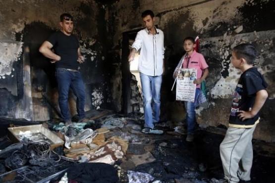 Palestinos observan los daños del incendio provocado en una casa por colonos israelíes por el que un bebé murió quemado. Foto: ANDES/AFP