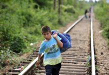 Un niño lleva sus pertenencias en un gran saco por las vías del tren que lo llevan, junto a otras pesonas, de Macedonia a Serbia. Crédito: UNICEF/Georgiev.