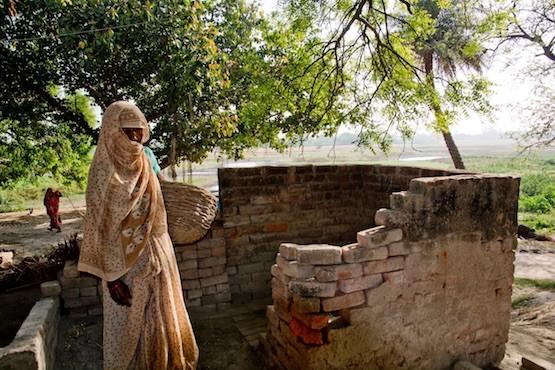 """Una mujer dalit junto al baño de una casa de casta alta en la localidad india de Mainpuri, donde se produjeron actos de violencia contra quienes intentan abandonar la profesión de """"recolectoras manuales"""" de heces. Crédito: Shai Venkatraman/IPS"""