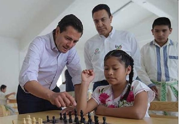 El presidente mexicano junto a una escolar y un tablero.