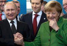 Vladimir Putin y Angela Merkel sonrientes y de la mano